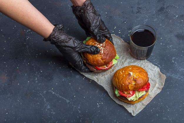 Vrouw in zwarte handschoenen met vers bereide gegrilde rundvlees hamburger. amerikaanse snack