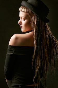 Vrouw in zwarte hoed en zwarte off shoulder top