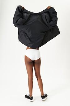 Vrouw in zwarte jas en wit ondergoed