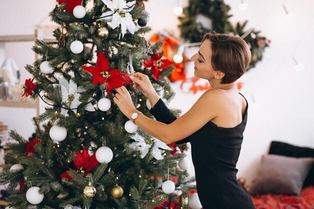 Vrouw in zwarte jurk door kerstboom