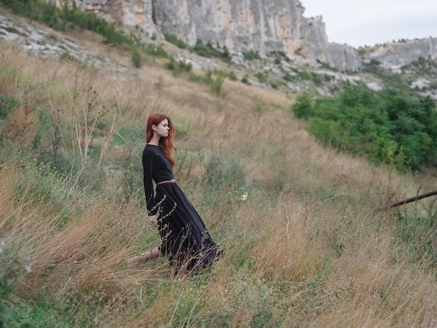 Vrouw in zwarte jurk in de bergen