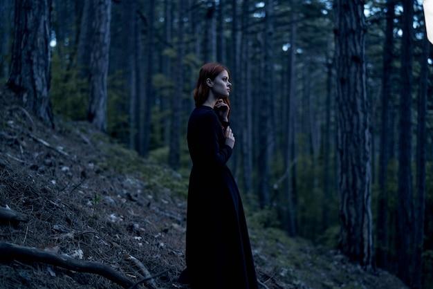Vrouw in zwarte jurk in het bos loopt frisse lucht