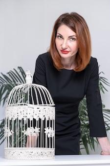 Vrouw in zwarte jurk legde haar handen op tafel. op tafel staat een wit metalen vogelkooi.