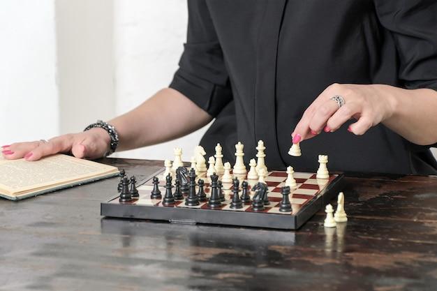 Vrouw in zwarte jurk met heldere manicure zit voor schaakbord en studeert schaaktheorie uit boek