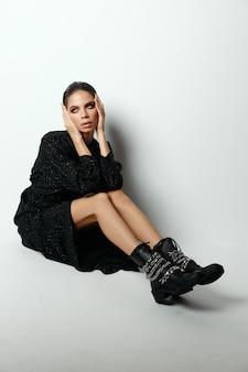 Vrouw in zwarte jurk zittend op de vloer lichte muur moderne mode.