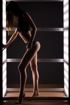 Vrouw in zwarte kant lingerie poseren tussen heldere lampen in een donkere kamer