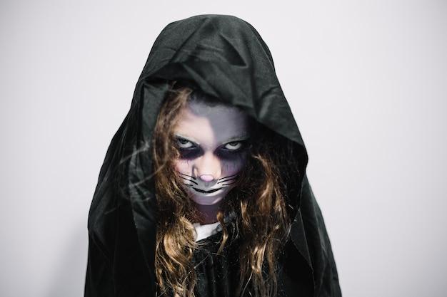 Vrouw in zwarte kap en gezichtverf