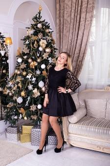 Vrouw in zwarte kleding dichtbij kerstmisboom thuis