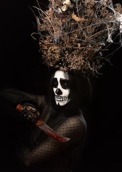 Vrouw in zwarte kleding en schedelmake-up, een kroon van droge takken en bloemen op haar hoofd