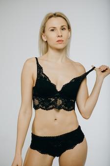 Vrouw in zwarte lingerie die op wit wordt geïsoleerd