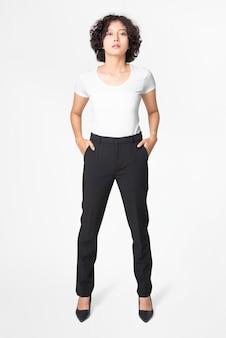 Vrouw in zwarte losse broek en wit t-shirt full body
