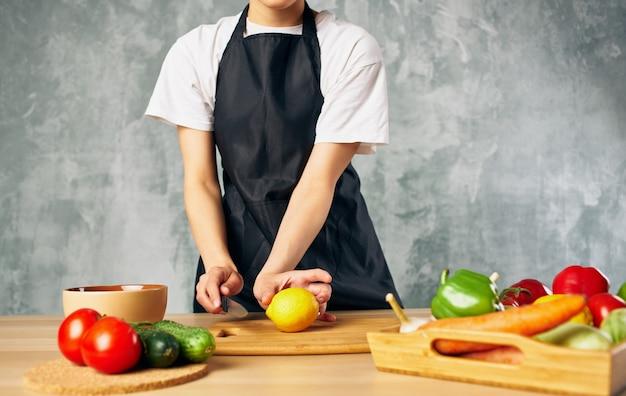 Vrouw in zwarte schort groenten keuken koken vers voedsel snijden.