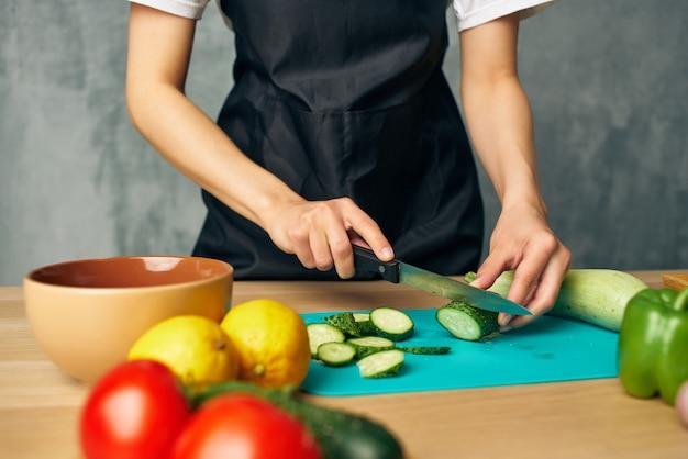 Vrouw in zwarte schort lunch thuis vegetarisch eten geïsoleerde background
