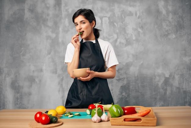 Vrouw in zwarte schort lunch thuis vegetarisch eten snijplank
