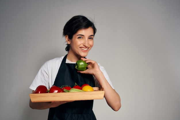 Vrouw in zwarte schort met een dienblad met verse groenten