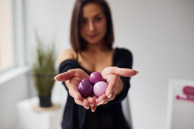 Vrouw in zwarte sexy kleding toont vaginale ballen en inbouwgereedschap in de kamer.