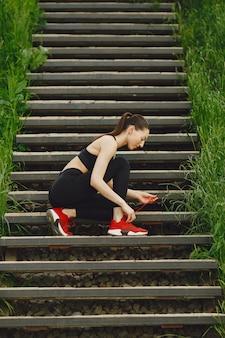Vrouw in zwarte spoerswear die zich op treden bevindt
