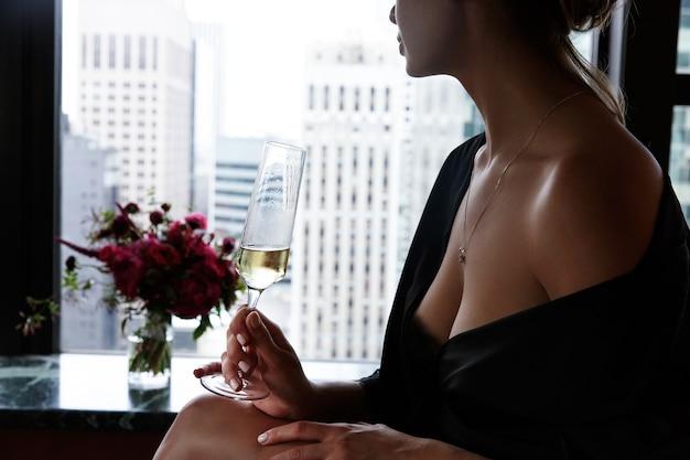 Vrouw in zwarte zijden gewaad met opne schouders en borst houdt glas met champagne