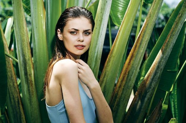 Vrouw in zwembroek in de buurt van groene bladeren van palmboom schone huid cosmetologie natuurlijke look