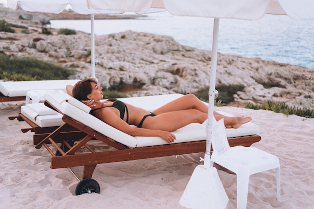 Vrouw in zwembroek ontspannen aan zee