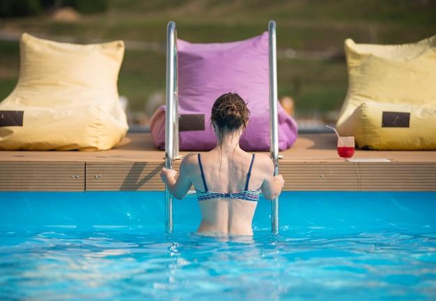 Vrouw in zwembroek uit het water van een zwembad