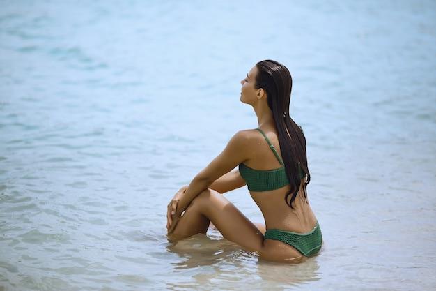 Vrouw in zwembroek zittend op het strand en kijken naar de zee. zijaanzicht van een prachtig meisje