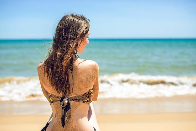 Vrouw in zwembroek zittend op strand