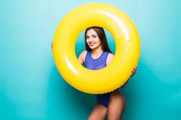Vrouw in zwempak binnen opblaasbare ring die over groene muur wordt geïsoleerd