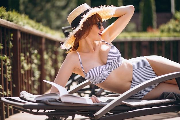 Vrouw in zwempak dat op een bed ligt en een boek leest