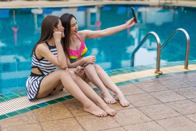Vrouw in zwempak die selfie foto op smartphone in zwembad maken