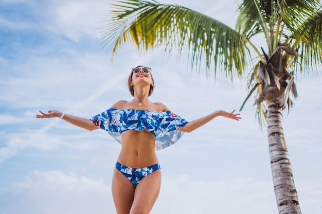 Vrouw in zwempak die zich bij het strand dichtbij de palm bevinden