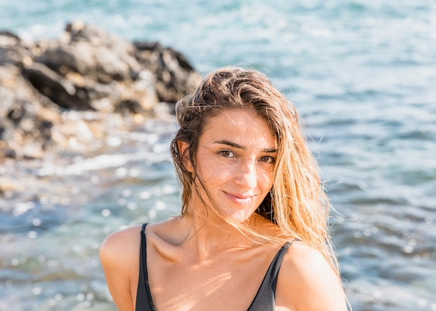 Vrouw in zwempak die zich op overzeese kust bevinden
