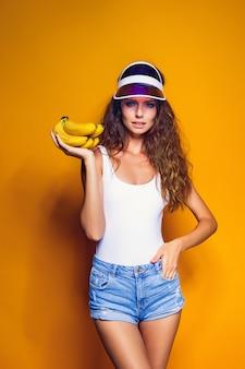 Vrouw in zwempak en blauwe borrels die banaan en stellen houden geïsoleerd over gele scène