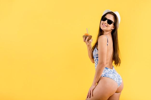Vrouw in zwempak met drank op strand