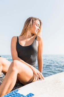 Vrouw in zwempakzitting op overzeese kust met surfplank