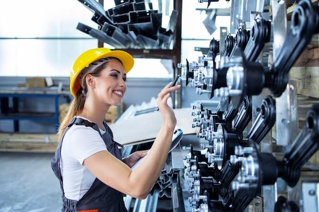 Vrouw industriële werknemer in uniforme en veiligheidshelm die productie in fabriek controleert