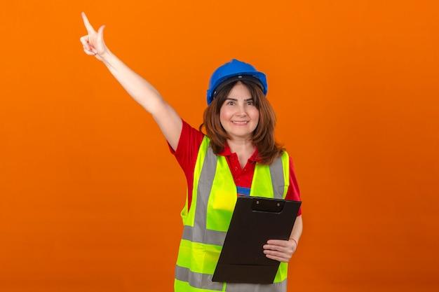 Vrouw ingenieur in bouw vest en veiligheidshelm klembord in de hand houden op zoek vertrouwen met een glimlach op blij gezicht wijst naar iets met vinger permanent over geïsoleerde oranje backgro