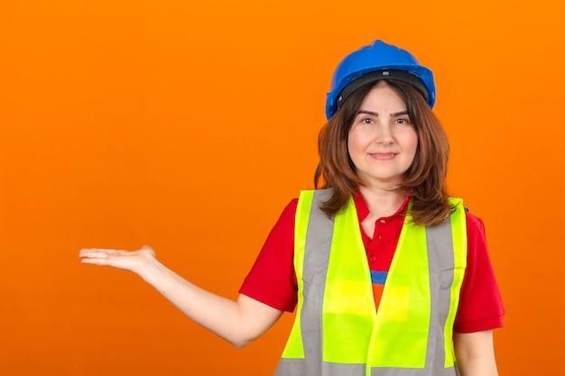 Vrouw ingenieur in bouw vest en veiligheidshelm presenteren en wijzen met de palm van de hand kopiëren ruimte kijken naar de camera met een glimlach op het gezicht over geïsoleerde oranje muur