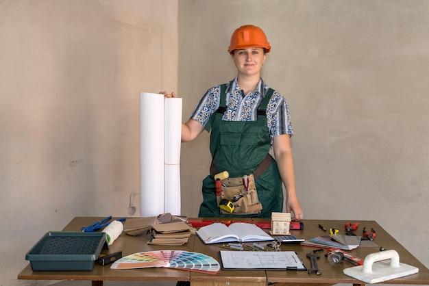 Vrouw ingenieur op werkplek met blauwdrukkenprint