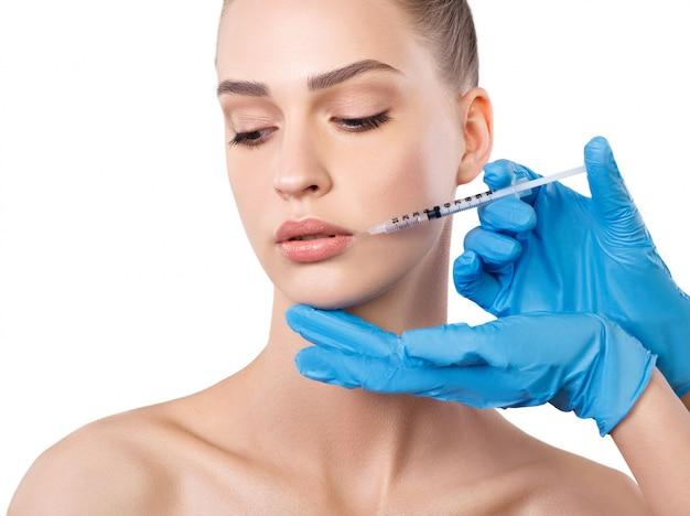 Vrouw injecties krijgen in de buurt van lippen. cosmetische behandeling