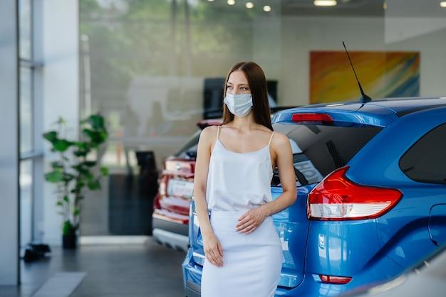 Vrouw inspecteert een nieuwe auto bij een autodealer in een masker tijdens de pandemie.