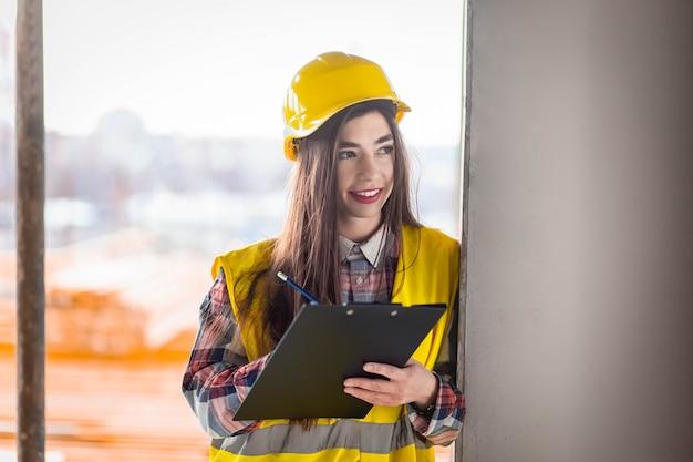 Vrouw inspecteert het gebouwenproces op een bouwplaats