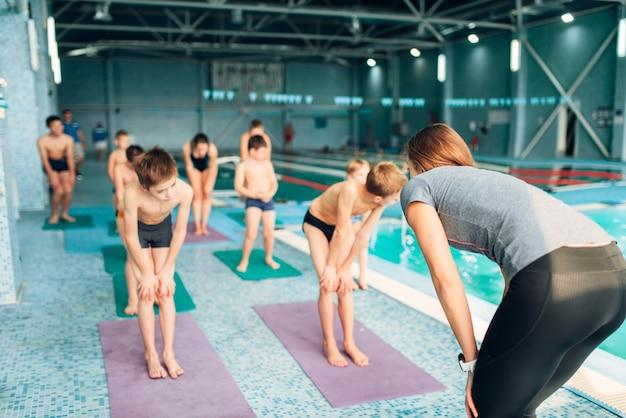Vrouw instructeur en groep kinderen doen oefeningen voordat ze zwemmen. gezond en gelukkig kinderconcept. sportieve kinderactiviteit in modern sportcentrum met zwembad.