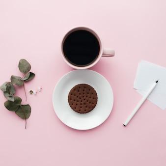 Vrouw internationale dag concept, koffiekopje, plaat, koekje, tak, notities, pen, eucalyptusbladeren op roze achtergrond. hoge kwaliteit foto