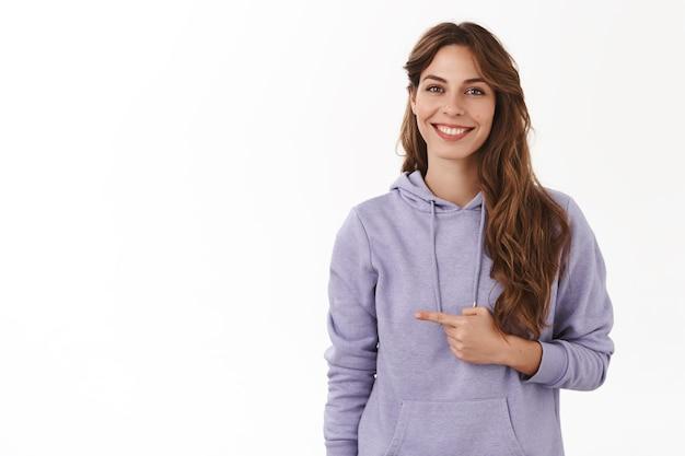Vrouw introduceert vriendin vrienden wijzend naar links wijsvingers glimlachen dom mooi bescheiden staand witte muur paarse hoodie met vermelding van smakelijk aanbod geven advies plukken promo