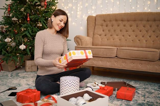 Vrouw inwikkeling kerstcadeau zittend op de carped in de woonkamer