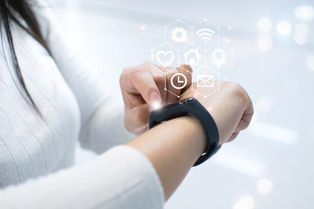 Vrouw is bezig met het opzetten van een slim horloge voor gebruik van innovatieve technologie. gemengde media, digitaal.
