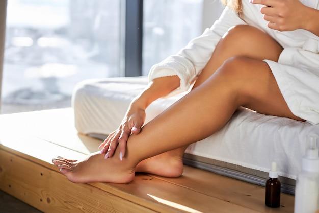 Vrouw is cosmetica crème toe te passen op benen, thuis, zittend op bed in badjas. schoonheidsconcept, bijgesneden foto van benen, close-up