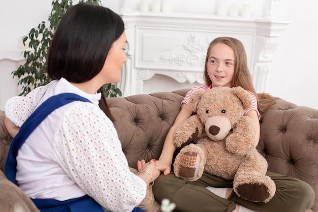 Vrouw is een professionele kinderpsycholoog in gesprek met een tienermeisje in haar gezellige kantoor