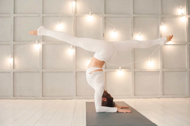 Vrouw is het beoefenen van yoga in een lichte studio. vrouw en yoga asanas.